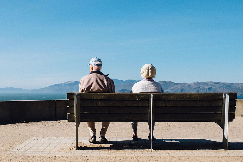 Senior couple sitting on bench looking at the ocean