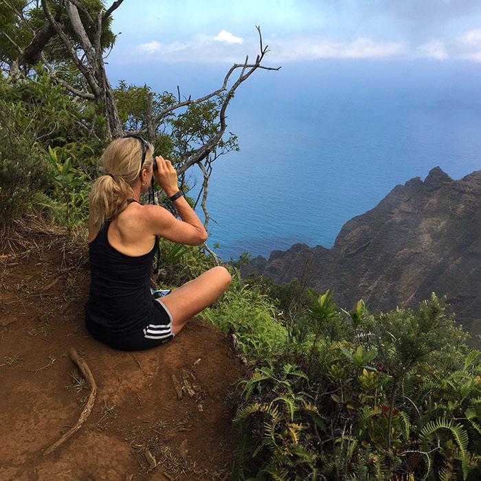 Dena sitting on ground at overlook in Hawaii