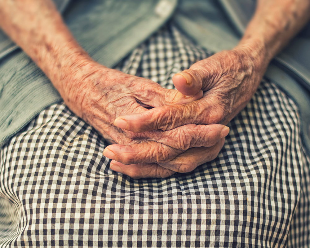 Elderly woman's wrinkled hands resting on her lap