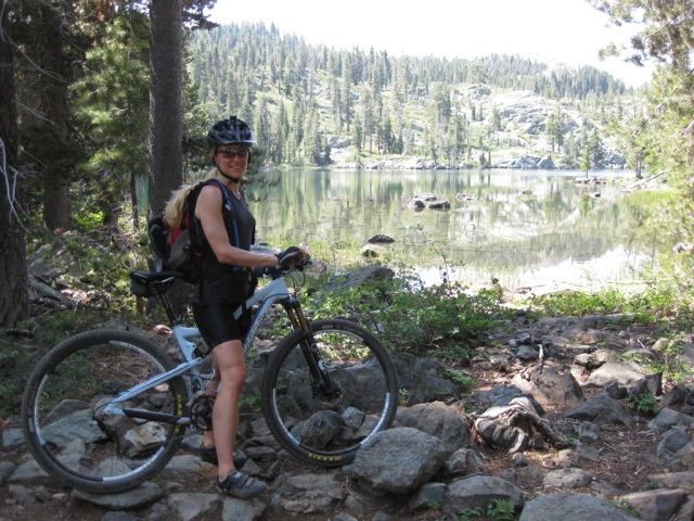 Dena on her mountain bike next to a lake