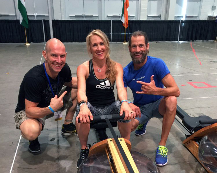 Dena Loijos on row machine posing with colleagues